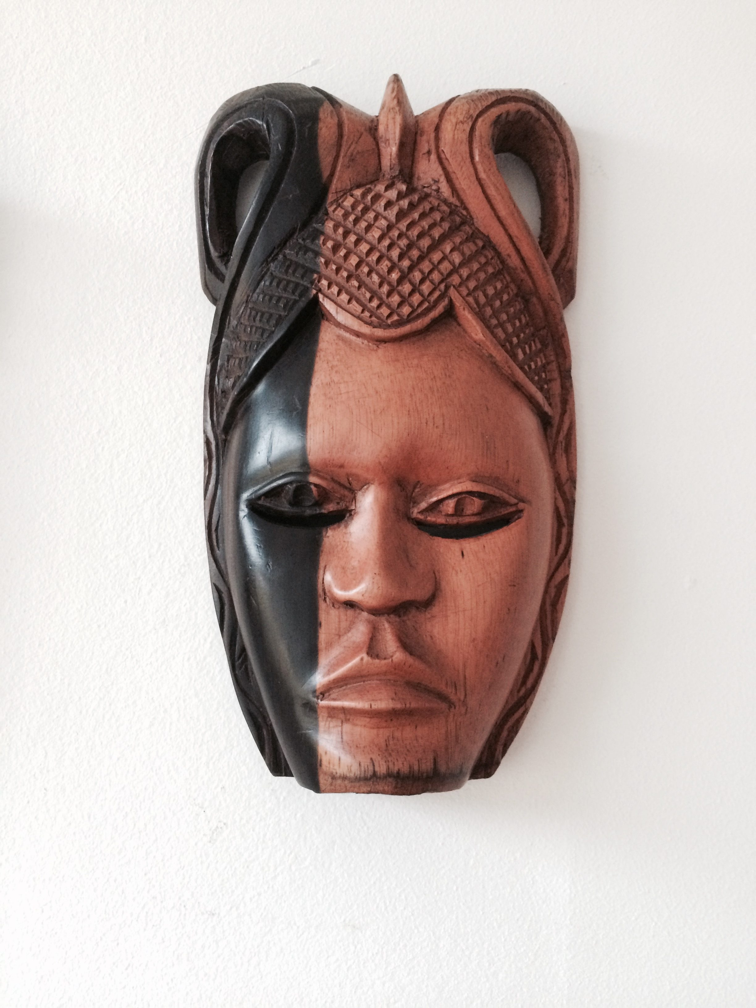small black and light brown african wooden mask